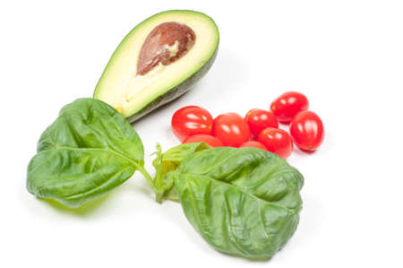 Avocado, cherry tomatoes and basil on the white background Stock Photo - 22224605