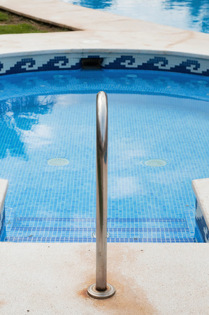 Blue swimming pool with stairs and banister Stock Photo - 22224608