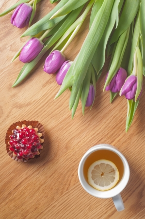 Fresh violet tulips on the wooden table, vertical photo