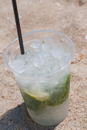 Shot of Mojito cocktail on the beach photo