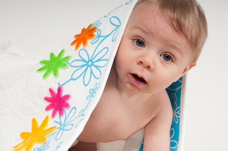 Baby boy in white towel with multicolored flowers Stock Photo - 22351322