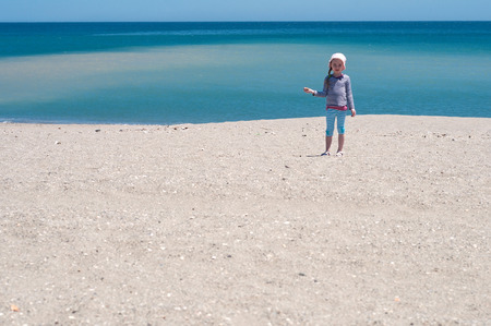 Little girl playing on the beach, coast and blue sea Stock Photo - 22351325
