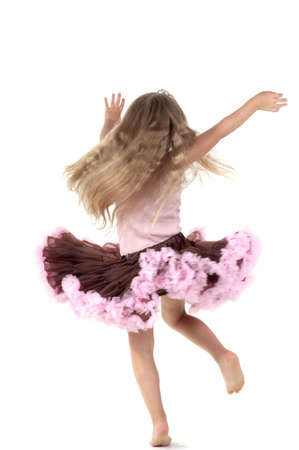 Shot of small dancing girl with long blond hair in studio