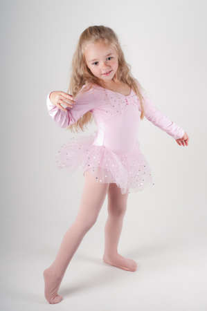 little girl dancing: Studio shot of ballet dancer girl in pink doing pas