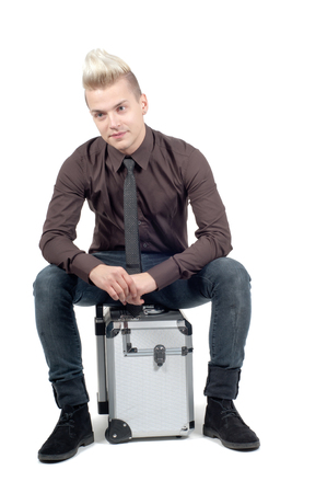 Handsome man sitting on the suitcase isolated on white Stock Photo - 22607775