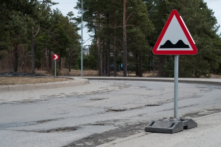 Shot of potholes on the road with sign photo