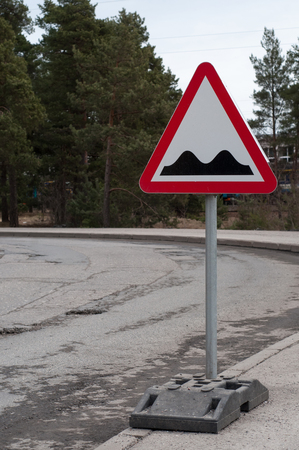 Shot of potholes on the road with special sign photo