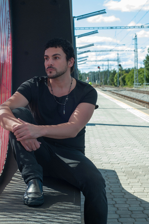 Shot of handsome man in black sitting on platform photo