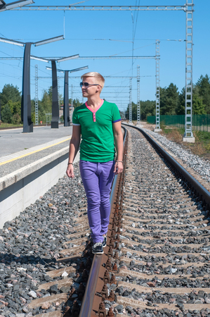Shot of one man walking on train tracks photo