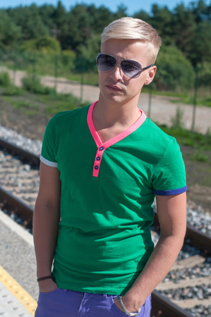 Shot of handsome man with sun glasses standing on platform photo