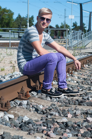 Shot of one man sitting on train tracks photo
