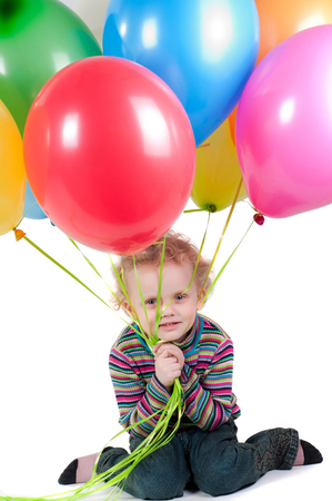 Little girl with multicolored air balloons sitting on the floor photo