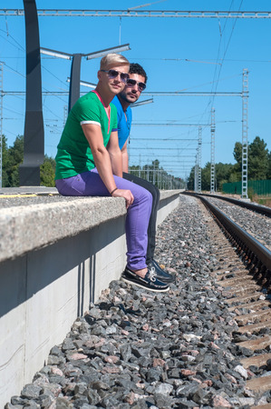 Shot of two young men sitting on platform photo