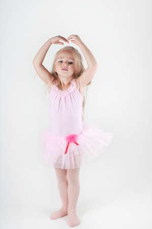 Studio shot of little ballet dancer girl doing pas photo