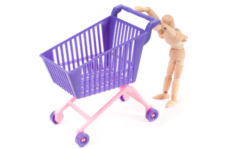 shoppingcart: Conceptual shot with miniature shopping-cart and wooden man isolated on white Stock Photo