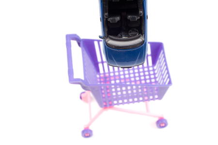 shoppingcart: Blue car falling into shopping-cart, isolated on white