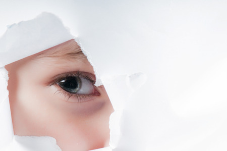 Child eye looking through a hole in a paper photo