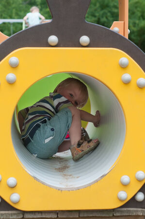 Young boy sitting in crawl tube on the playground photo