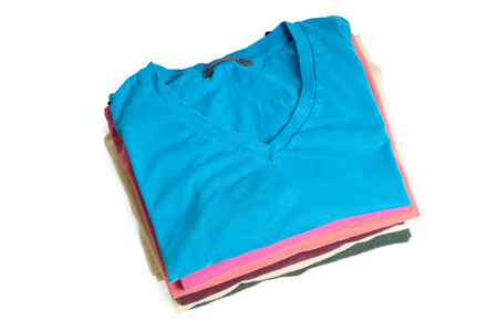Stack of colored t-shirts on the light background