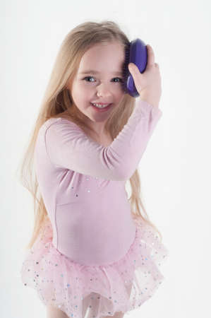 Little girl combing long blond hair in studio photo