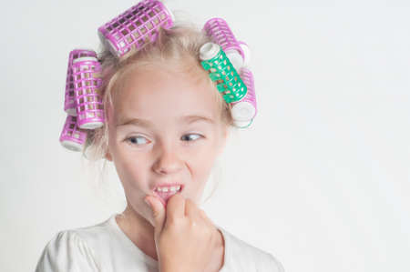 Portrait of little girl in hair-curler, studio photo
