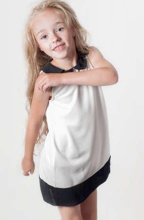 Little girl in white dress in studio photo