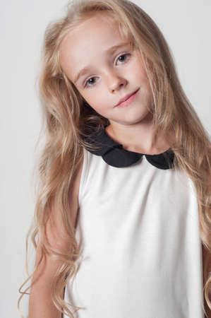 Little cute girl in white dress in studio photo