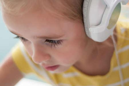 Portrait of little blond girl in headphones photo