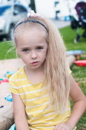Portrait of beautiful little girl with long hair watching on you photo