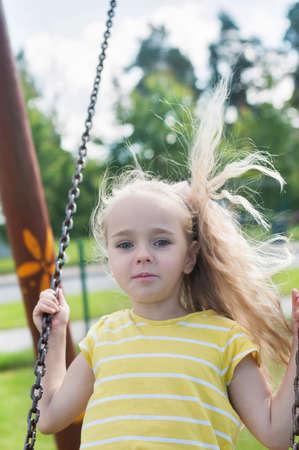 Happy little girl swinging on a swing photo