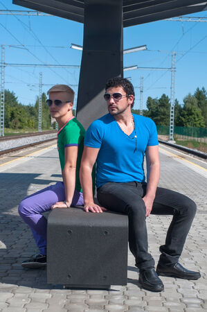 Shot of two handsome guys sitting on platform photo