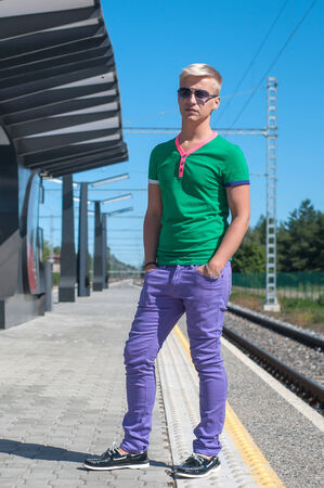 Shot of stylish man with sun glasses standing on platform photo