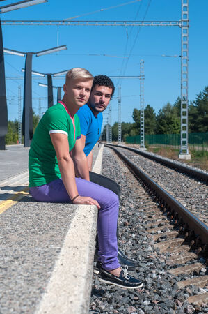 Two young trendy men sitting on the platform photo