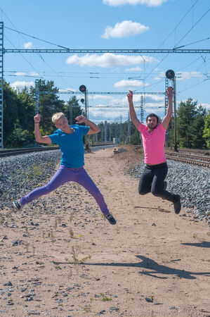 Two handsome young guys jumping near rail track photo