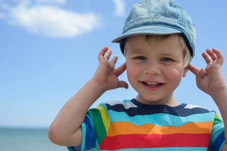 Small boy holds his hands over ears not to hear Stock Photo