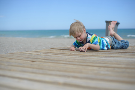 Boy resting on a wooden walkway on the beach Stock Photo