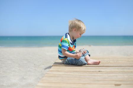 Boy sitting on a wooden walkway on the beach
