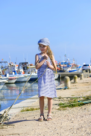 Little girl on the harbor holding a rope photo