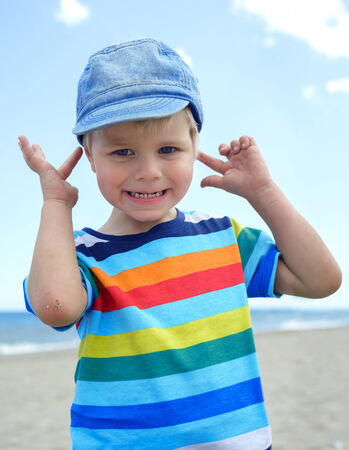 Small boy holds his hands over ears not to hear photo