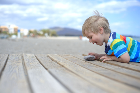 Boy playing on a wooden walkway on the beach photo
