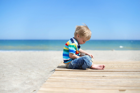 Boy sitting on a wooden walkway on the beach photo