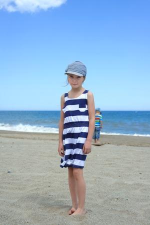 Serious cute little girl on the beach photo