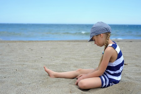 Serious cute little girl sitting on the beach photo
