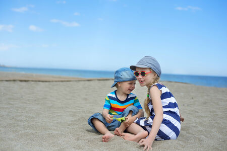 Two small kids sitting on the beach photo