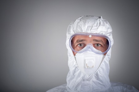 Scientist in protective wear, glasses, respirator photo