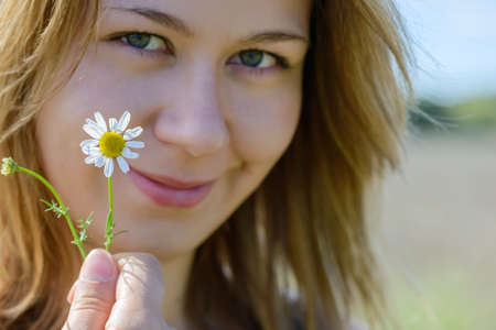 Portrait of young woman with camomile photo