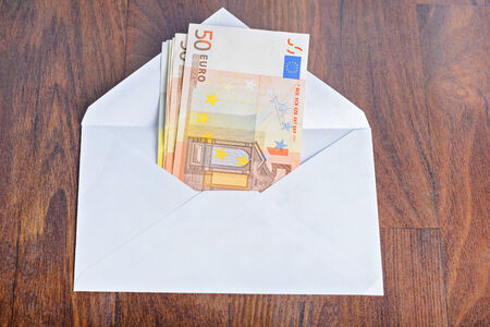 remuneration: Open envelope with euro banknotes on table