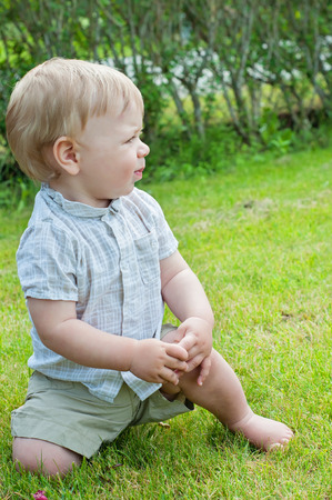 Baby boy sitting on green grass photo
