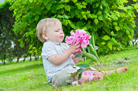 Small baby boy holding a flower in his hand photo