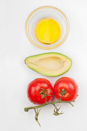 Top view to the tomatoes, avocado and olive oil photo